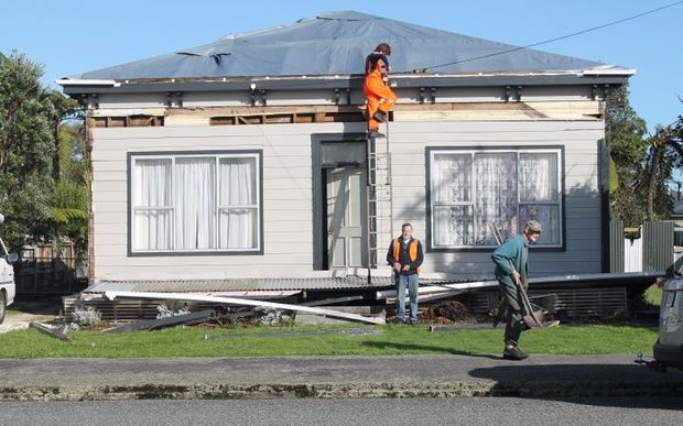 William Lomax-Sawyer on ladder and Ash Bradley from Buller Electricity restore power to one of the thousands of homes which lost power.