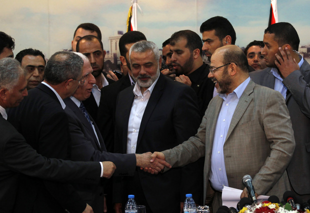 Fatah delegation chief Azzam al-Ahmed (centre left) and Hamas deputy leader Musa Abu Marzuk shake hands on the deal.