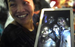 A happy family member shows the latest picture of the missing boys taken by rescue divers inside Tham Luang cave.