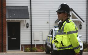 A police officer stands guard outside a residential address in Amesbury, a man and woman were found unconscious.