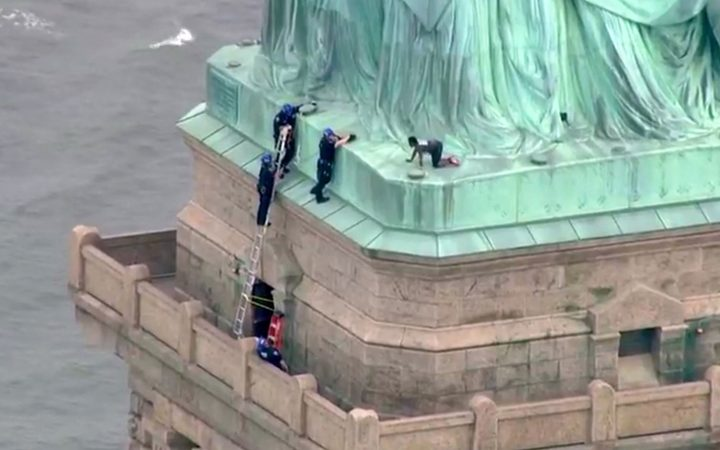 Police talk to a woman who climbed to the base of the Statue of Liberty