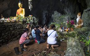 Family members pray before a shrine in Tham Luang cave area as operations continue for the 12 boys and their coach trapped at the cave in Thailand.
