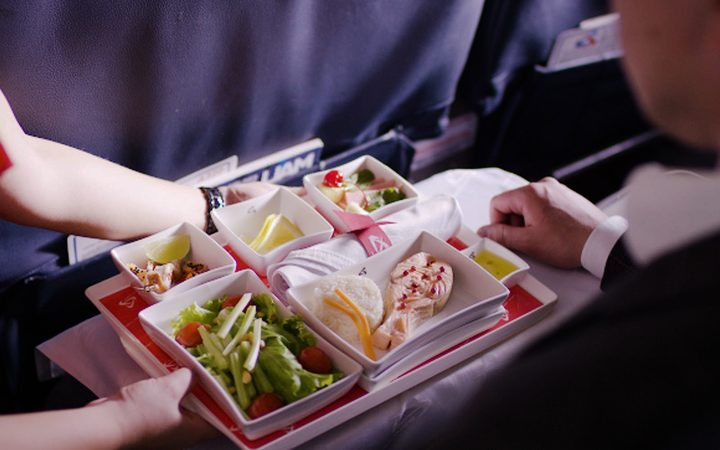 Stewardess holding tray with airline food on blue background.