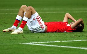 Russian player Aleksandr Erokhin lies on the ground in disappointment.