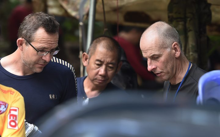 Two British divers John Volanthen (L) and Richard William Stanton (R) are seen with Thai rescue personnel at the Tham Luang cave area on July 3, 2018 after finding the children and football coach alive in the cave.