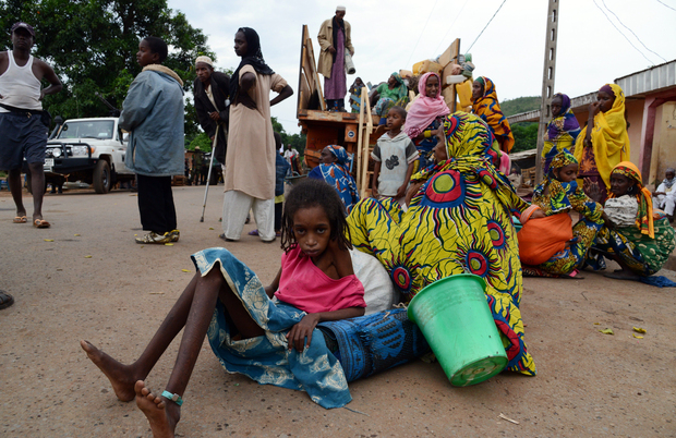 A girl sits on the pavement as a vehicle loaded with people and goods, part of a convoy of vehicles carrying Muslims from the PK12 district, outside of Bangui, gets ready to leave the city.