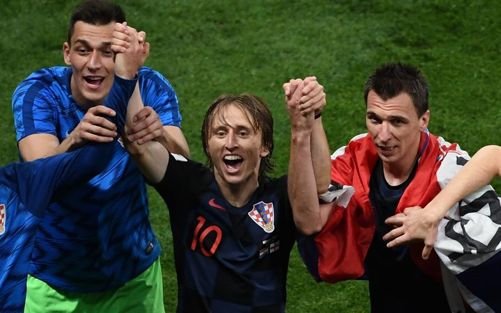 Croatian midfielder Luka Modric (C) and forward Mario Mandzukic (R) celebrate after winning the Russia 2018 World Cup semi-final football match against England.