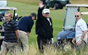 US President Donald Trump (C) gestures as he walks during a round of golf on the Ailsa course at Trump Turnberry, the luxury golf resort of US President Donald Trump, in Turnberry, southwest of Glasgow, Scotland, during the private part of his four-day UK visit.