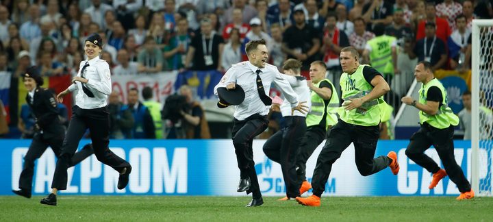 Stewards remove pitch invaders during the Russia 2018 World Cup final football match between France and Croatia at the Luzhniki Stadium in Moscow on July 15, 2018.