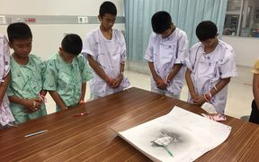 "This handout photo released by the Ministry of Health shows members of the rescued ""Wild Boars"" football team at hospital in Chiang Rai province bowing their heads after writing messages on a drawing of former Navy SEAL diver Saman Kunan who died  during the rescue mission."
