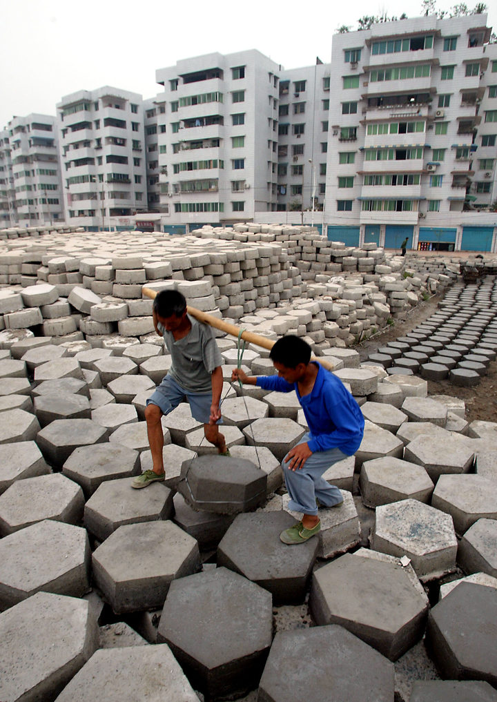 Workers carry the cement slabs which will be laid along the banks of the Yangtze River, to prevent soil erosion at the new Fengdu town with newly built apartments blocks in the background, upriver from the giant Three Gorges dam project, 16 June 2003.