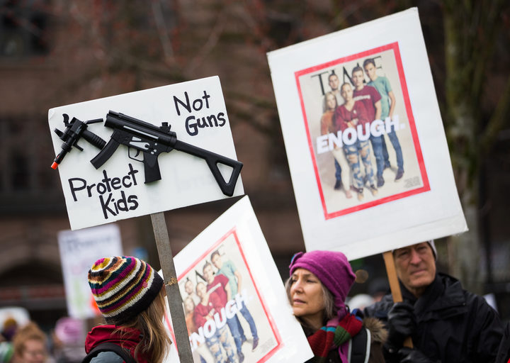 People hold signs during the March for Our Lives rally for Marjory Stoneman Douglas High School students in March 2018 in Seattle, Washington.