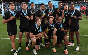 The New Zealand men's sevens team with the World Cup trophy.