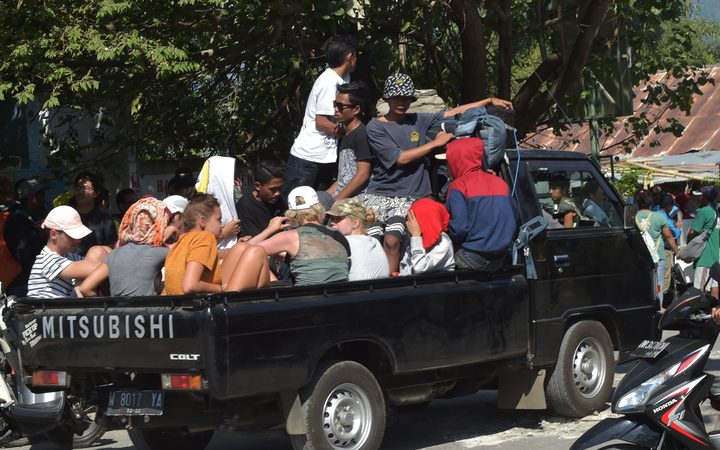 Foreign tourist and local residents ride on the back of a vehicle in Bangsal, North Lombok
