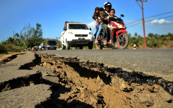 A oar car past a damage road at Kayangan subdistrict in North Lombok on West Nusa Tenggara province on August 8, 2018, three days after an earthquake hit the area.