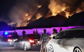 People watch flames from the Holy Fire outside Glen Ivy Hot Springs in Corona, California, southeast of Los Angeles, on August 10, 2018.