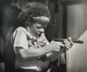 Boy with Davy Crockett hat and mock pistol, 1956.
