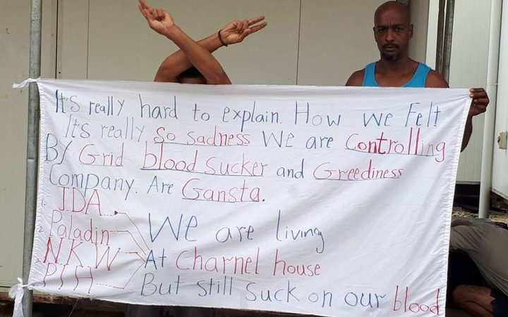 Bashir Osman displays one of his protest banners.
