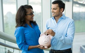 77306946 - closeup portrait, two smart professionals in blue shirts holding piggy bank, isolated office indoors background. powerful financial and banking business solutions, decisions concept