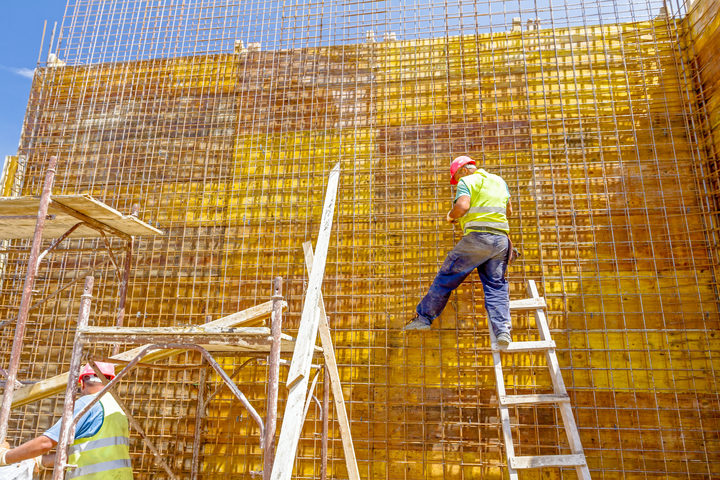 Construction worker is binding rebar for tall reinforced concrete construction.