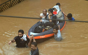 Rescuers wade through the water at Companypady in kozhikode, Kerala