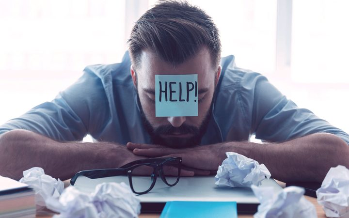 41257198 - he needs help. hopeless young beard man with adhesive note on his forehead leaning at the desk and keeping eyes closed while sitting at his working place in office