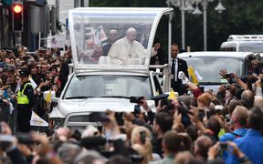 Pope Francis waves to the faithful on his popemobile in Dublin on August 25, 2018, during his visit to Ireland to attend the 2018 World Meeting of Families.