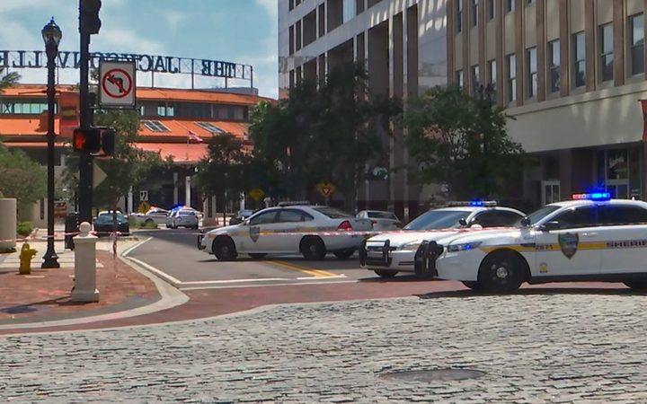 Police cars block a street leading to the Jacksonville Landing area in downtown Jacksonville after a mass shooting at a video game tournament.