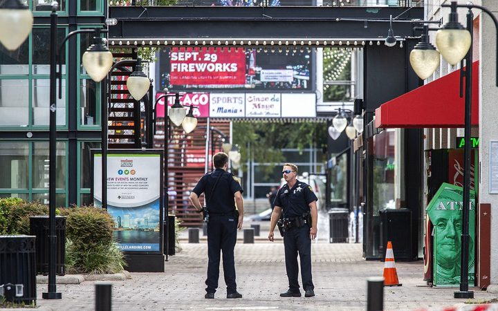 Jacksonville Sheriff's officers patrol around the ships at Jacksonville Landing  after a shooting rampage during a video game tournament at the site claimed four lives.