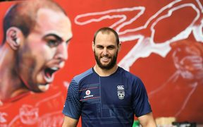 Simon Mannering in front of a mural for his 300th match created by artist Emily Gardner aka Adore.