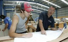 A boat builder and apprentice on the job.
