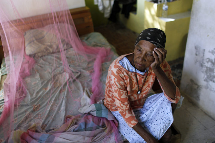 Aurea Cruz, 66 sits on her bed inside her house damaged by Hurricane Maria in Viegues, Puerto Rico.