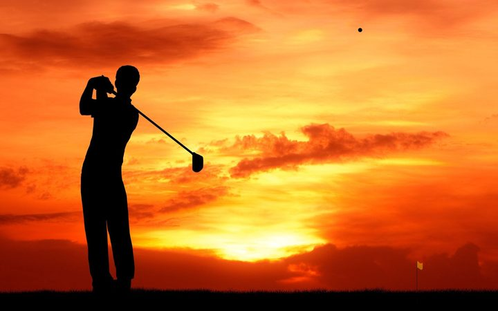 13224828 - male golfer hit golf ball toward the hole at sunset silhouetted