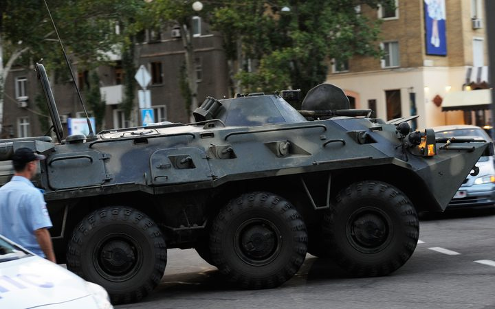 An armoured vehicle rides in the street in Donetsk, eastern Ukraine, after Alexander Zakharchenko was killed