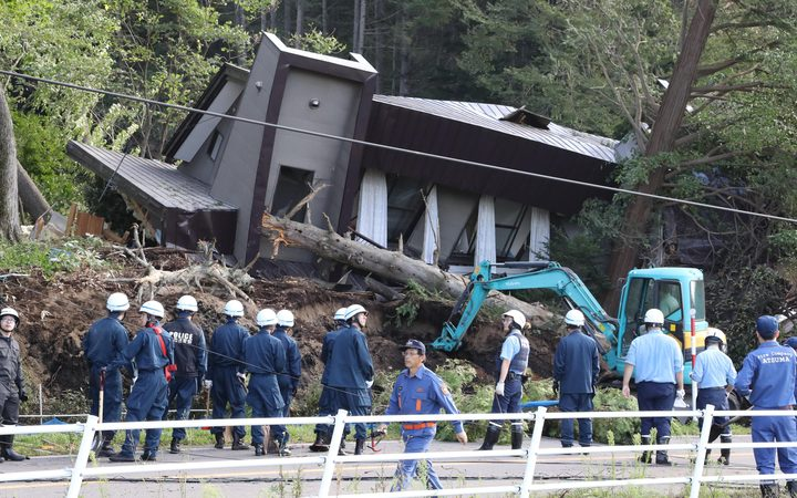 Police officers and fire crews at at a collapsed house in Atsuma, Hokkaido
