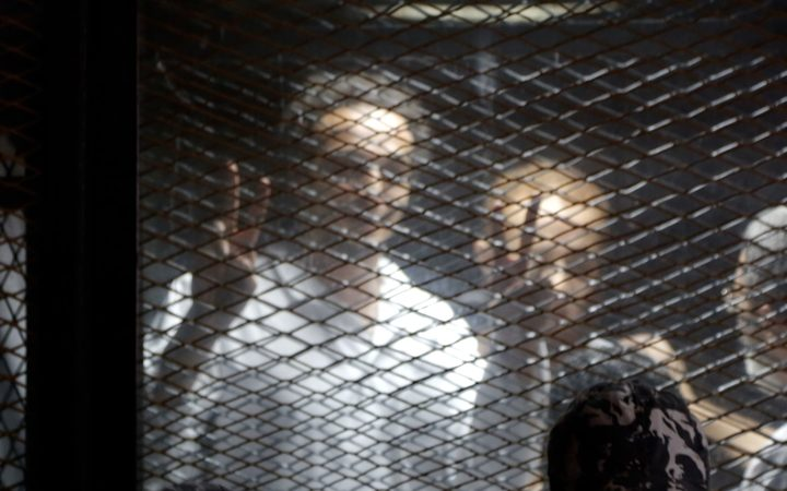 Egyptian photojournalist Mahmoud Abu Zied, known by his nickname Shawkan, gestures in a soundproof glass cage inside a makeshift courtroom in Tora prison in Cairo, Egypt