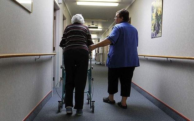 A rest home nurse helping an elderly patient.
