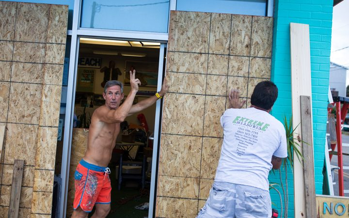 A shop owner boards up his Wrightsville Beach, North Carolina, building.