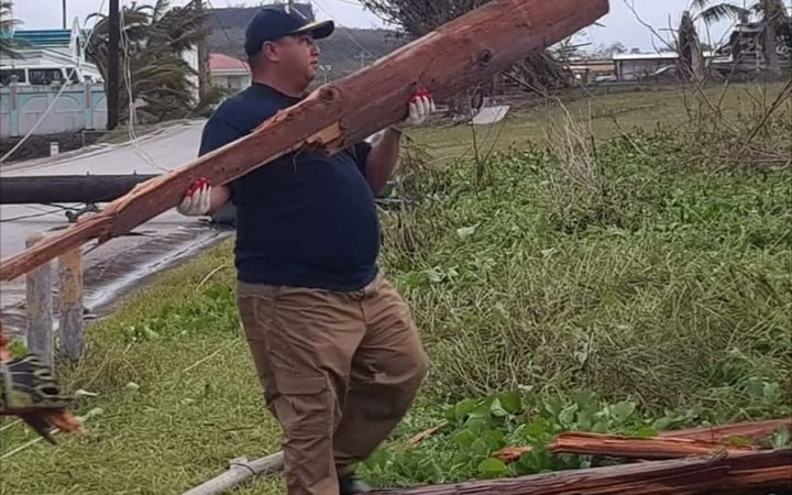 Governor Ralph Torres assists with the clean-up effort after Typhoon Mangkhut