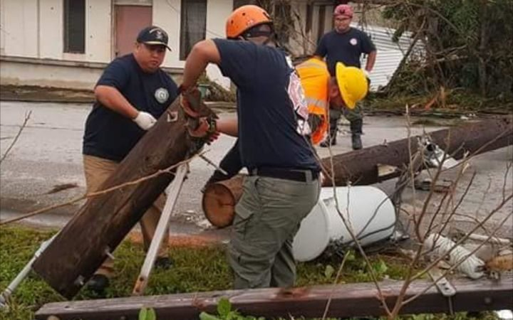 Governor Ralph Torres, (left), helps clear debris