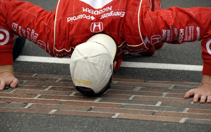 Scott Dixon does the traditional kissing of the bricks after winning the 92nd running of the Indy 500 in 2008.