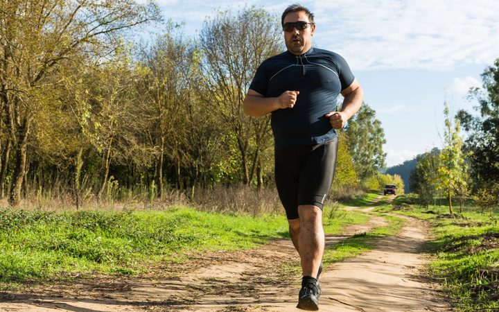 67035726 - big belly man jogging , exercising, doing cardio in the park , slightly overweight, loosing weight. on a lawn of green grass between trees without leaves.