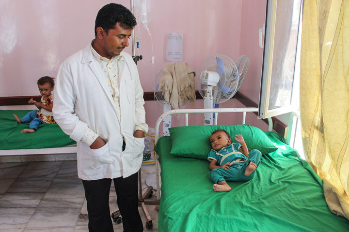 A hospital staffer looks at a Yemeni child suffering from malnutrition lying on a bed at a hospital in the northern district of Abs in the northwestern Hajjah province on September 19, 2018.
