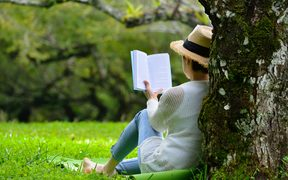 Woman sitting under a tree reading a book in the park