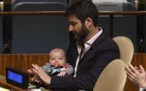 Clarke Gayford with his daughter Neve Te Aroha Ardern Gayford, as Prime Minister Jacinda Ardern speaks during the Nelson Mandela Peace Summit at the UN.