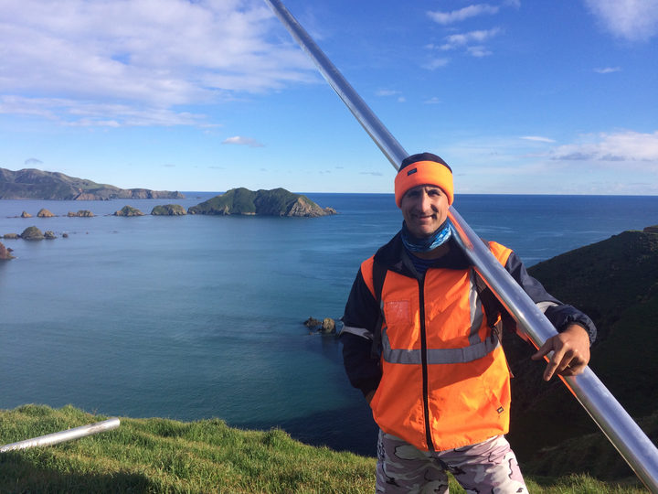 Dr Dan Hikuroa at Rangitoto ki te Tonga holds an aluminum core tube as part of fieldwork research.