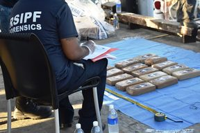 A Forensic officer in Solomon Islands recording the amount of cocaine being off-loaded from the yacht Vieux Malin in Honiara.