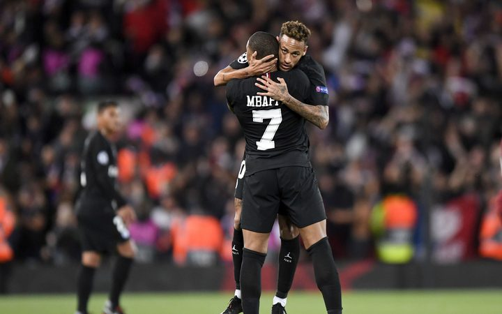 Kylian Mbappe and Neymar of Paris St Germain embrace.