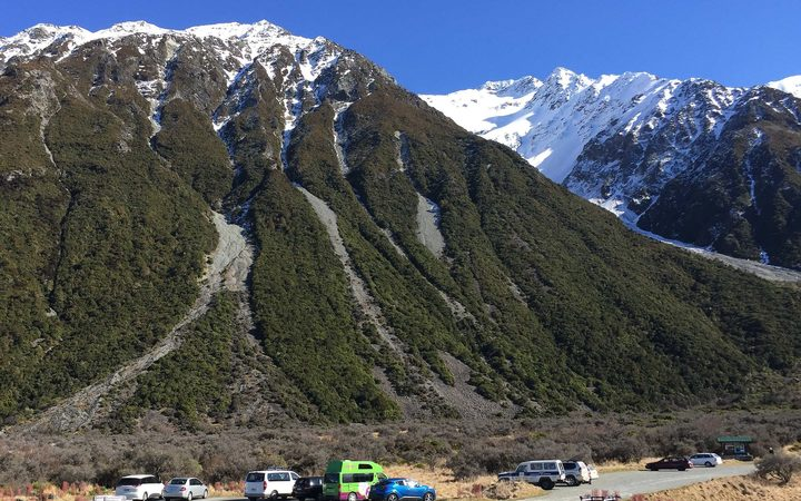 Blue skies and snow capped mountain with cars at base