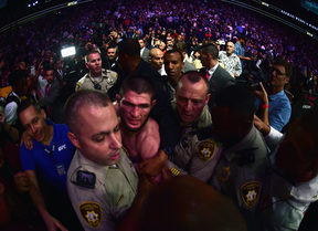 Khabib Nurmagomedov of Russia is escorted out of the arena after defeating Conor McGregor.